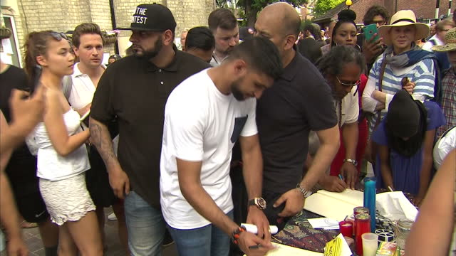 shows exterior shots boxer amir khan walking through crowd and signing book of condolences for grenfell tower victims. locals and volunteers have... - co ordination stock videos & royalty-free footage