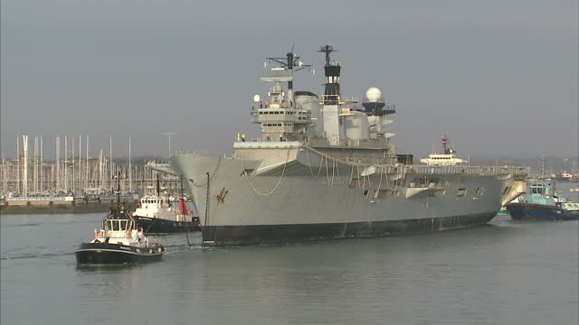 shows exterior shots british navy aircraft carrier hms illustrious being towed away from portsmouth harbour by tug boats with people standing on deck... - hms illustrious r06 stock videos and b-roll footage
