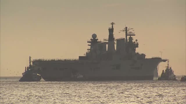 shows exterior shots british navy aircraft carrier hms illustrious being towed out of the solent from portsmouth harbour on it's last voyage... - hms illustrious r06 stock videos and b-roll footage