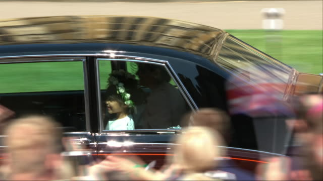 Shows exterior shots car containing the page boys and flower girls driving through the invited guests in the grounds of Windsor Castle and heading...