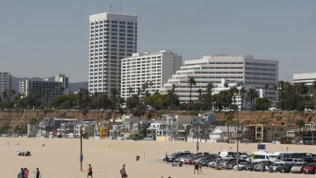 shows exterior shots cars filling parking lot with santa monica beach in background and highrise buildings and beach front proerties overlooking the... - 見渡す点の映像素材/bロール