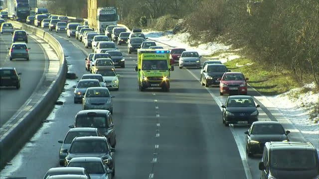 Shows exterior shots cars in traffic jam on dual carriageway moving out of way of ambulance as it drives down middle of raod with siren and emergency...