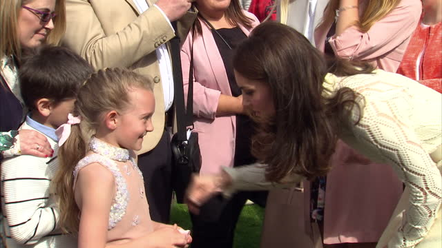 Shows exterior shots Catherine Duchess of Cambridge talking to guests including children at a Buckingham Palace Garden Party The Duke and Duchess of...