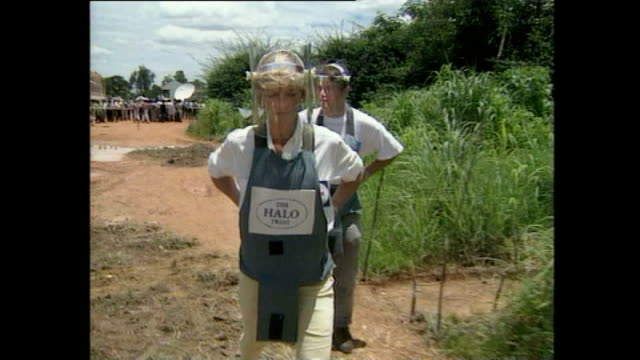 Shows exterior shots charity workers clearing landmines from field Exterior shots Princess Diana wearing protective body armour walking through field...