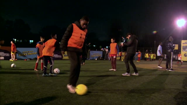 shows exterior shots children practising football skills at youth scheme backed by premier league and tottenham hotspur football club in order to... - sports league stock videos & royalty-free footage