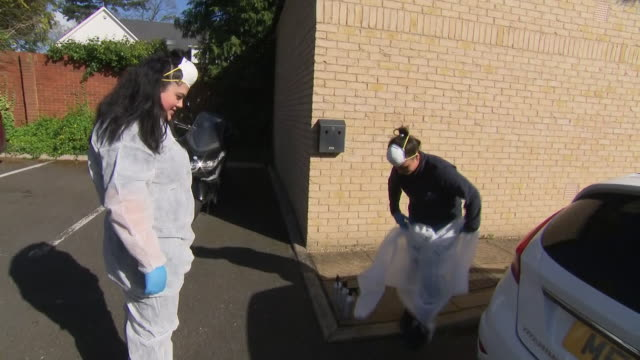 shows exterior shots cleaners getting dressed in protective coveralls and facemasks before entering property to provide a deep clean against... - phase image stock videos & royalty-free footage