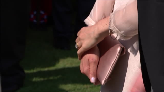 vidéos et rushes de shows exterior shots close up meghan markle, duchess of sussex, hands with engagement and wedding rings on finger holding clutch bag at an official... - garden party