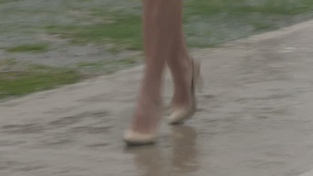 Shows exterior shots close up of anonymous feet walking through rain wearing high heel shoes and wellington boots on November 29 2016 in Bridgetown...