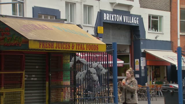 shows exterior shots closed fresh fruit shop with brixton village market in background and market stall selling fruit with people walking past... - ブリックストン点の映像素材/bロール