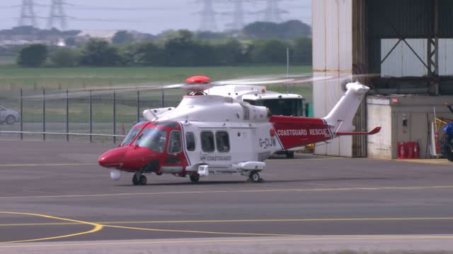shows exterior shots coastguard search and rescue helicopter with rotors turning on ground next to hanger on may 29 2016 in folkestone england - helicopter rotors stock videos and b-roll footage