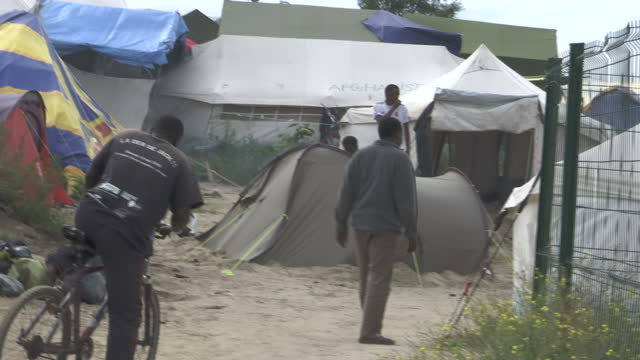 shows exterior shots conditions in the jungle migrant camp in calais with garden planted outside makeshift shelter rubbish outside tent drinking... - tyre swing stock videos & royalty-free footage