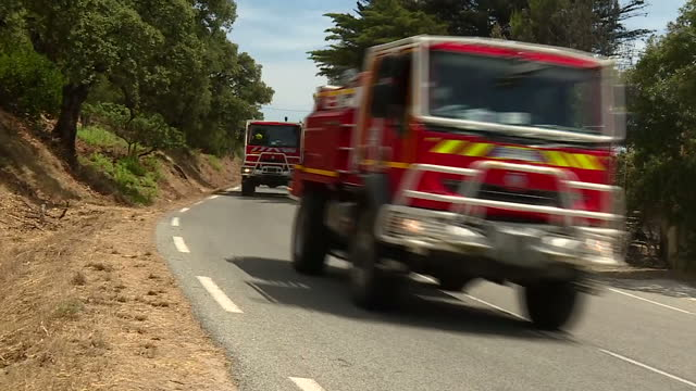 vídeos y material grabado en eventos de stock de shows exterior shots convoy of fire fighting emergency vehicles driving past along road in area affected by wildfires. the mayor of a french seaside... - var