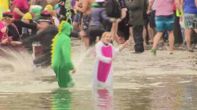 Shows exterior shots couple dressed in dinosaur onesies wading through shallow water laughing after New Year's Day Loony Dook Swim Edinburgh's...