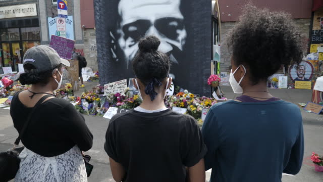 shows exterior shots crowd at rally, most with face masks, looking at tributes and memorial to death of george floyd in minneapolis. get your knee... - minnesmärke bildbanksvideor och videomaterial från bakom kulisserna
