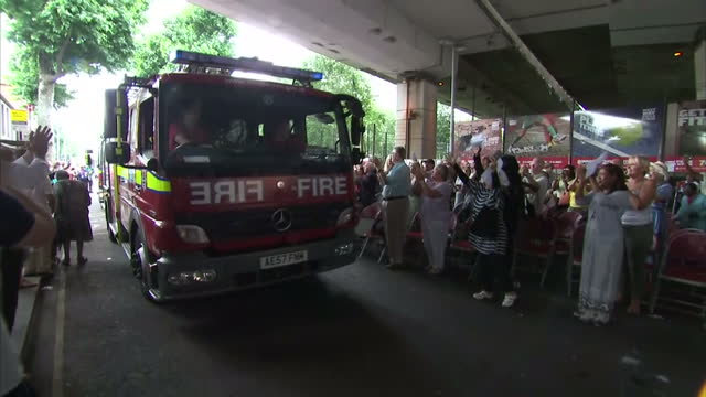 shows exterior shots crowd cheering and applauding fire crew as they leave grenfell tower in fire engine after their shift finishes. locals and... - co ordination stock videos & royalty-free footage