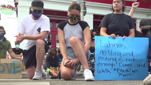 shows exterior shots crowd of people taking the knee on black lives matter protest march in over killing of george floyd. huge protests against the... - ひざまずく点の映像素材/bロール