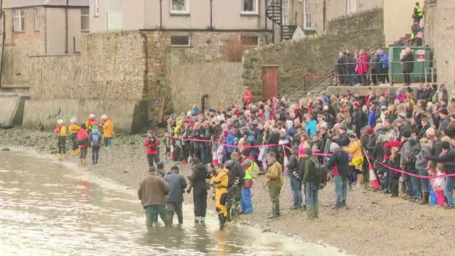 shows exterior shots crowds including photographers arriving and lining balconys and banks of firth of forth ready for the loony dook swimmers.... - fluss firth of forth stock-videos und b-roll-filmmaterial