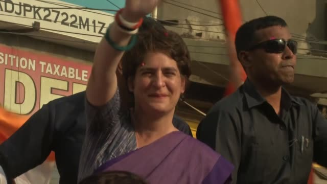 Shows exterior shots crowds of fans surrounding car containing Priyanka Gandhi as she campaigns for her brother during elections Exterior shots...