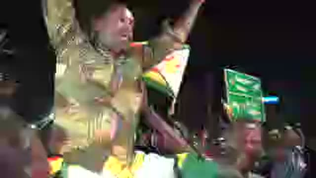 Shows exterior shots crowds of happy Zimbabweans celebrating in the street shouting singing dancing and waving huge Zimbabwe flags and hoisting...