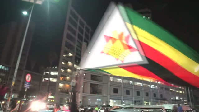 Shows exterior shots crowds of happy Zimbabweans celebrating in the street shouting singing dancing and waving huge Zimbabwe flags He was once...