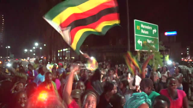 shows exterior shots crowds of happy zimbabweans celebrating in the street shouting singing dancing and waving huge zimbabwe flags he was once... - 2017 bildbanksvideor och videomaterial från bakom kulisserna