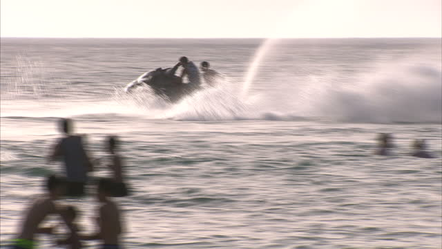 shows exterior shots crowds of people on tripoli beach with someone on jet ski in the water. on june 06, 2015 in tripoli, libya. - acquascooter video stock e b–roll