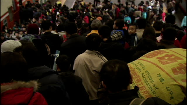 shows exterior shots crowds of people walking onto train platforms carrying sacks of possessions onto trains on january 17 2009 in beijing china - bahnreisender stock-videos und b-roll-filmmaterial