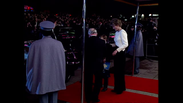 Shows exterior shots crowds waiting outside the cinema in Leicester Square and Princess Diana with Prince William and Prince Harry leaving after the...