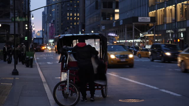 shows exterior shots customers flagging down a pedicab, bicycle taxi, talking to driver and climbing on board for ride in manhattan in new york city... - pedicab stock videos & royalty-free footage