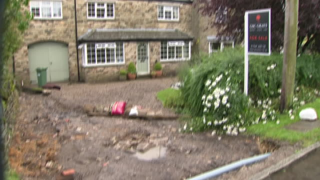 shows exterior shots damaged houses and driveways with written off cars after flash floods ripped through the village of Bellerby in the Yorkshire...
