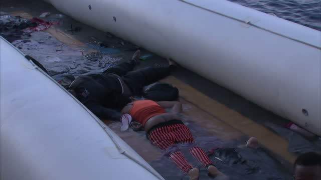 shows exterior shots dead bodies of migrants in bottom of the dinghy they tried to cross the mediterranean in drowned during a rescue attempt made by... - flüchtling stock-videos und b-roll-filmmaterial