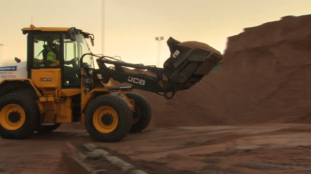 Shows exterior shots digger moving sand and salt used to grit roads from one pile onto another at depot on 28th December 2017 in Oldham Greater...