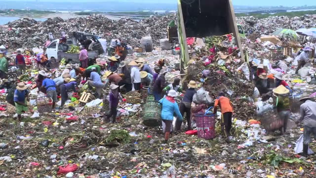 Shows exterior shots diggers moving rubbish around landfill site with workers picking plastic out of piles of rubbish The fourth World Ocean Summit...