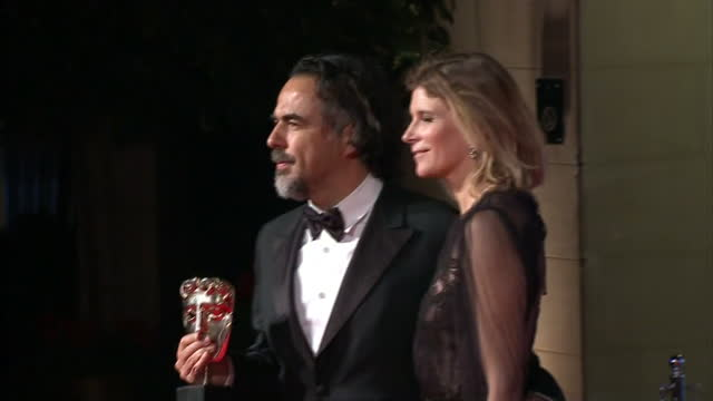 Shows Exterior shots director Alejandro Gonzalez Inarritu posing for photos and talking to Press on red carpet on arrival at Grosvenor House Hotel...