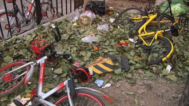 shows exterior shots dockless shared bikes tossed over fences and thrown into central reservation on road where users abandoned them. shared bike... - abbandonato video stock e b–roll