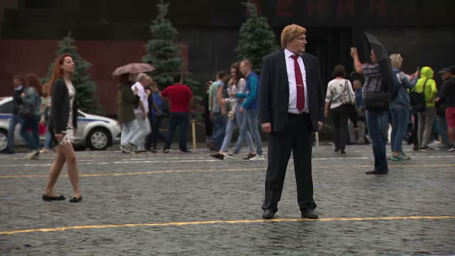 shows exterior shots donald trump impersonator trying to attract tourists for photos in red square in moscow exterior shots russian flag flying near... - doppelgänger stock-videos und b-roll-filmmaterial