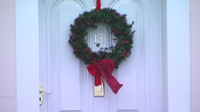 shows exterior shots door number 13 with christmas wreath around it and red bow blowing in wind as storm eleanor approaches west coast of england on... - リース点の映像素材/bロール