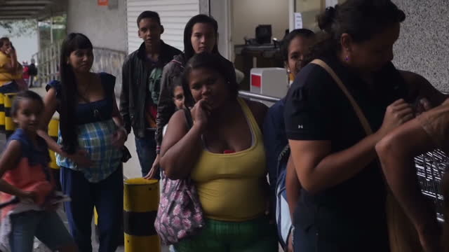 shows exterior shots driving past a 5 hour long queue to buy food from supermarket and people moving forward at front of queue. venezuela -- a... - venezuela stock videos & royalty-free footage