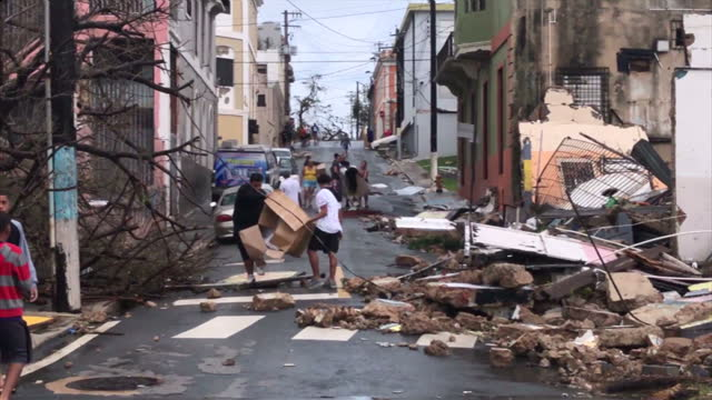 vídeos de stock, filmes e b-roll de shows exterior shots driving through streets in san juan after hurricane maria passed showing debris littering floor fallen teres damaged power lines... - porto riquenho
