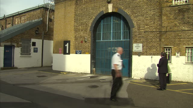 shows exterior shots entrance to hmp brixton prison and prison guard walking past gate exterior shots prison yard in middle of prison and interior... - prison guard stock videos and b-roll footage