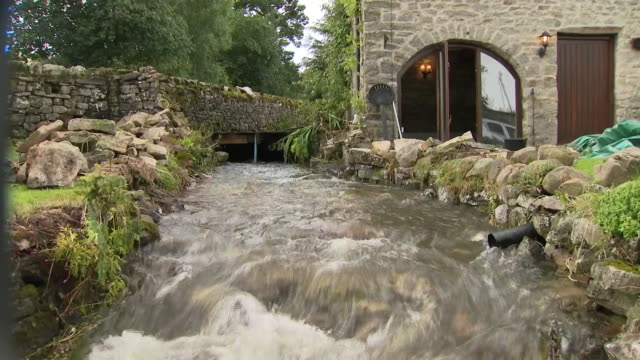 Shows exterior shots fast running stream and sandbags piled nearby after flash floods ripped through the village of Bellerby in the Yorkshire Dales...