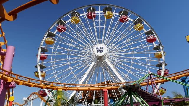 shows exterior shots ferris wheel and roller coaster at pacific park amusement park on santa monica pier on 26th july 2017 in santa monica beach... - 観覧車点の映像素材/bロール