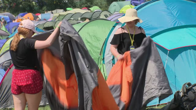 Shows exterior shots festival goers setting up tents at Glastonbury Festival campsite in the sun and heat on 22nd June 2017 in Glastonbury Somerset...