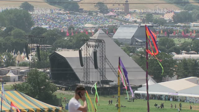 Shows exterior shots fields of Glastonbury getting covered by tents of festival goers Exterior shots people looking very hot walking through...