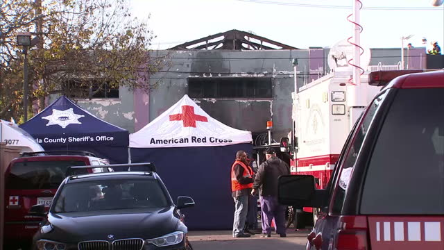 Shows exterior shots fire damaged warehouse with emergency services at the scene conducting investigation and recovering bodies Exterior shots local...