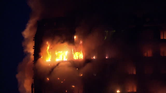shows exterior shots fires burning across all upper floors of grenfell tower with close up shots of flames burning through windows on some floors... - fire natural phenomenon stock videos and b-roll footage