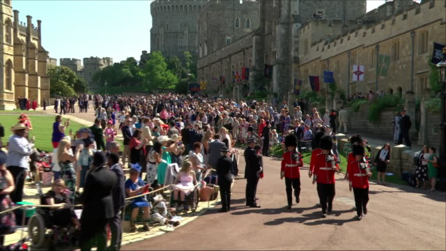 vidéos et rushes de shows exterior shots five royal guard soldiers marching through the grounds of windsor castle past invited guests waiting for the wedding of prince... - monarchie