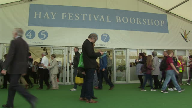 vídeos de stock e filmes b-roll de shows exterior shots flags fluttering and crowds of people walking about at hayonwye literary festival exterior shots bookshop tent at hayonwye on... - hay on wye