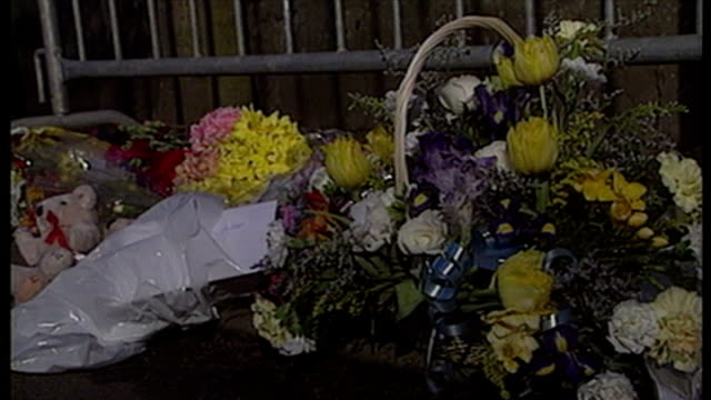 shows exterior shots floral tributes teddy bears and messages left outside grounds to the school in memory of the victims of the dunblane school... - dunblane school massacre stock videos & royalty-free footage