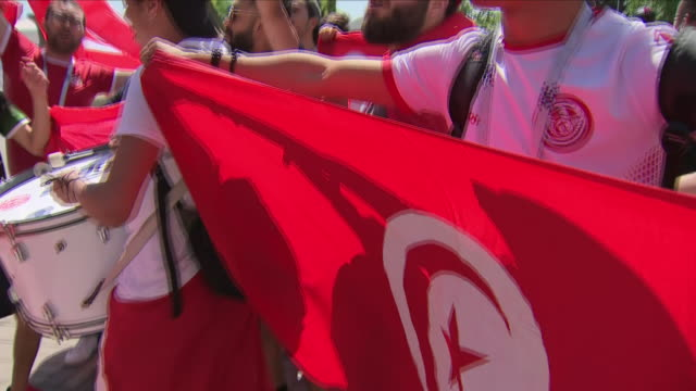 shows exterior shots football fans from tunisia waving flags drumming and chanting as they walk along street ahead of the 2018 world cup opening... - tunisia stock videos & royalty-free footage